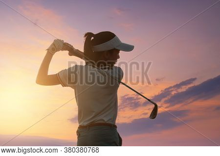 Young Women Asia Player Golf Swing Shot On Course With Sunset Sky Twilight Background. Exercise And