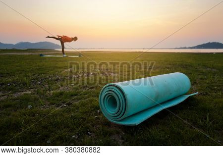 Yoga Mat On Grass In Nature At Sunset With Blurry Woman Yoga Practice Background After The Covid-19