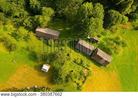 Aerial Drone View Of Old Wooden Hut On Mountain Slope. Stable For Cattle And Barn Near Hut, Green We