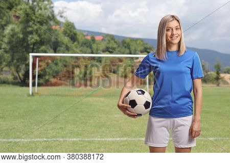 Female soccer player holding a ball under arm and standing on a football pitch