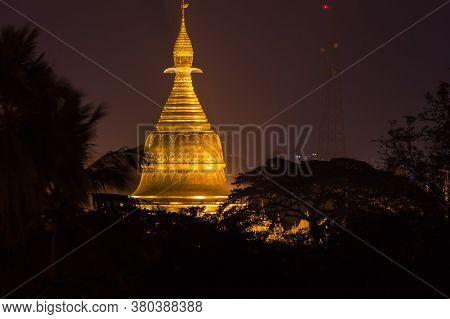 The Shwedagon Pagoda Illuminating In The Night Sky Over Yangon, Myanmar