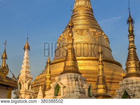 Evening Light Falling On The Golden Shwedagon Pagoda In Yangon, With A Blue Sky Background