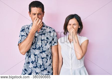 Beautiful couple wearing casual clothes smelling something stinky and disgusting, intolerable smell, holding breath with fingers on nose. bad smell