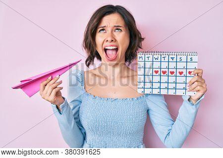Young beautiful woman holding heart calendar and paper airplane angry and mad screaming frustrated and furious, shouting with anger looking up.
