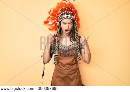 Young beautiful latin woman wearing indian costume angry and mad raising fists frustrated and furious while shouting with anger. rage and aggressive concept.