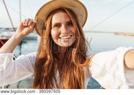 Image of cheerful ginger woman smiling and taking selfie photo while walking on promenade