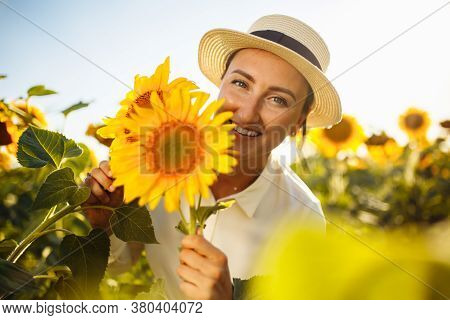 Beauty Joyful Young Woman With Sunflowers Enjoying Nature And Laughing On Summer Sunflower Field. Fe