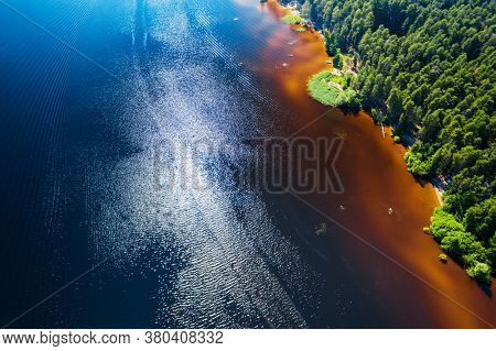 Aerial view of the river with orange water and coniferous coast