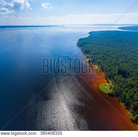 Aerial view of the river with orange water and coast with coniferous forest