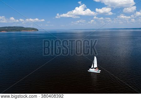 Aerial view of the calm river with catamaran sailing on it during summer day