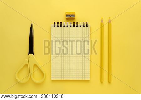 Yellow Notepad With A Spring, Yellow Pencil And Yellow Scissors On A Yellow Background. Monochrome H