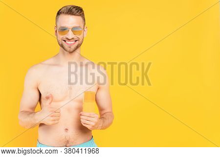 Muscular Man In Sunglasses Showing Thumb Up And Holding Bottle With Sunblock Isolated On Yellow
