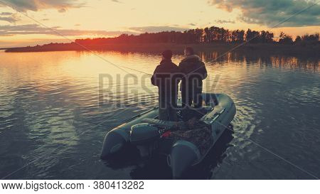 Two anglers fishing on the river at sunset