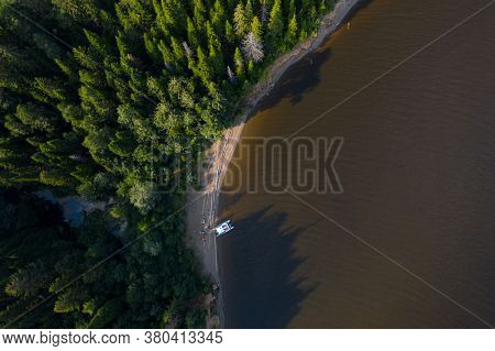 Aerial view of the wild narrow beach with anchored white vessel
