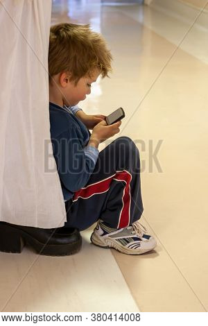 sitting down on mother shoes, portrait of a small Caucasian child sulking when he loses a game in the phone