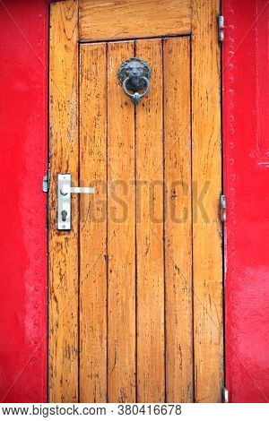 Red And Brown Entrance Door To A Houseboat Displayed Outdoors.