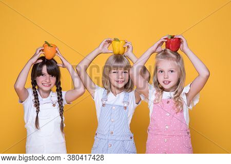 Group Of Three Beautiful Girls Holding In Hands Yellow, Orange, Red Peppers In Background In Studio,