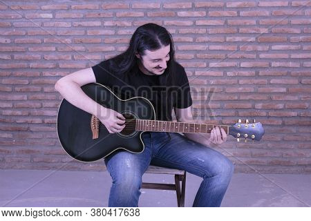 Young Male Performer Playing Guitar Sitting On A Chair.