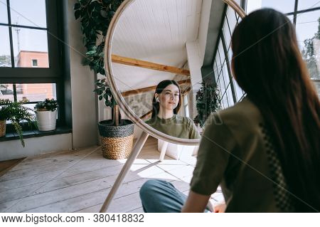 Attractive Young Caucasian Woman In Headphones Touching Face And Looking At Mirror In Living Room At