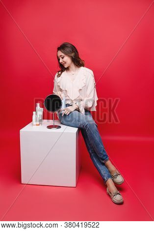 Beautiful Woman Chooses A Cosmetic Product, Studio Photo On A Red Background. Cosmetology And Person