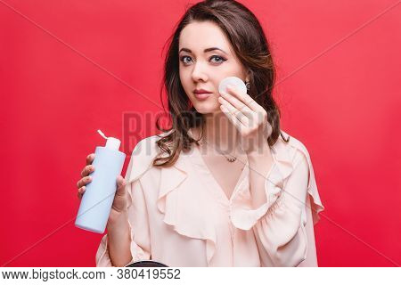 Beautiful Woman Holding A Cotton Pad And A Cosmetic Product In Her Hands, Studio Photo On A Red Back