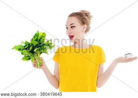 Beautiful Woman Chooses Between Cake And Salad, Over Isolated White Background. The Concept Of Healt