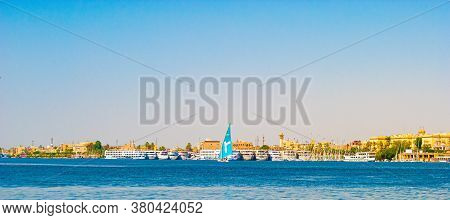 A Sailboat In The Nile River And The Luxor Temple In Egypt