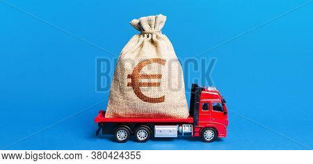 The Truck Is Carrying A Huge Euro Money Bag. Great Investment. Anti-crisis Measures Of Government. A