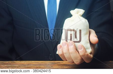 A Businessman Holds In His Hand A Israeli Shekel Money Bag. Stimulating Economic Recovery. Providing
