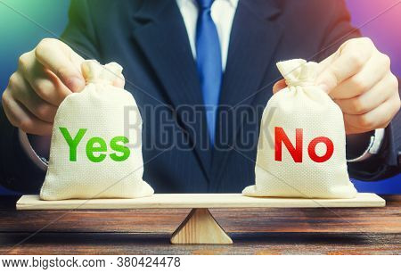 A Businessman Holds Yes And No Bags On Scales. Assessing Problem And Choosing Right Solution. Advant