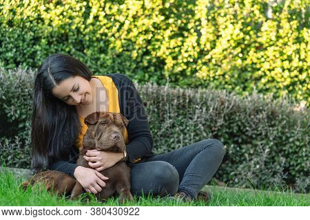 Hispanic Woman Sitting On The Grass Embracing Her Dog, A Shar Pei Labrador Mix.