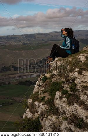 Brunette Woman Sitting At The Top Of A Mountain And Contemplating The Landscape. Travel Concept. Ver