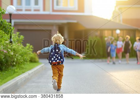 Little Schoolboy Joyfully Running To School After Holiday. Child Meeting With Friends. Education For