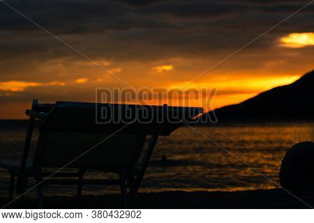 Late Bright Orange Sunset On The Zlatni Rat Beach In Bol. Dark Outline Of A Deck Chair On The Sea, P