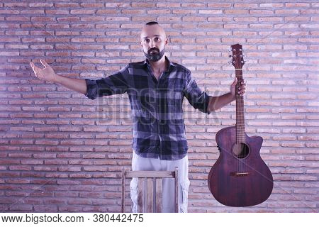 Proud Young Adult Male Holding An Acoustic Guitar After A Performance.