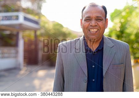 Portrait Of Happy Mature Overweight Indian Businessman In Suit Outdoors