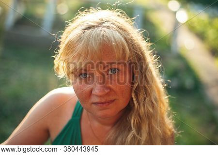 Portrait of a woman with light brown hair in the village.