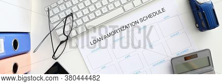 White Calendar With Loan Amortization Shedule Sign Closeup Background. Right Bank Credit Concept