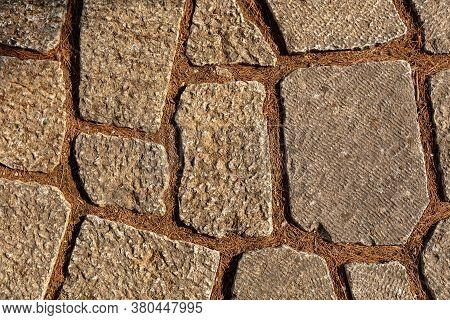 The Background Of The Floor Is Laid Out From Stones Of Various Shapes, In The Cracks Of A Needle Fro