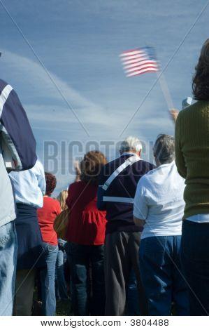 Woman Waving American Flag At Campaign Rally