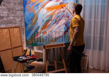 Young Man With Painting Skill Working On Large Canvas In Art Studio. Modern Artwork Paint On Canvas,