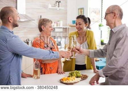 Family Making A Toast In Kitchen With Wine. Various Chees On Wooden Plate.