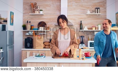 Man Singing On Red Pepper In Kitchen Making Wife Smile. Girlfriend Preparing Salad. Cooking Preparin