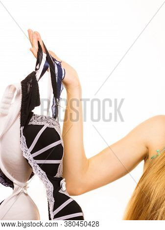 Bosom Concept. Female Hand Holding Many Bras, Choosing Which Bra To Wear, On White