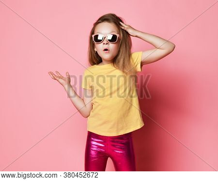 Puzzled 6-7 Y.o. Blonde Kid Girl In Yellow T-shirt, Shiny Pink Leggings And Sunglasses Scratches Her