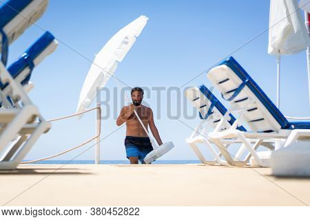 Man on beach jetty moving parasol