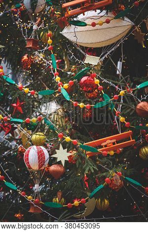 Evergreen Tree With A Variety Of Toys And Sparkling Garlands. New Year Decorations In The Center Of