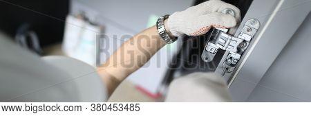 Close-up Of Carpenter Installing Wooden Door Hinges. Worker Using Protective Helmet And Gloves. Empl