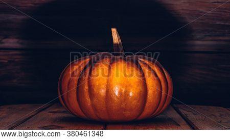 Halloween Pumpkin In Horror Lighting On Wooden Floor With Copy Space