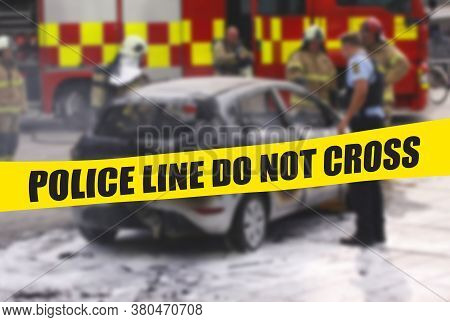 Police Officer And Firefighters Standig At Burnt Out Car Wreck With Yellow Police Tape With Text Pol